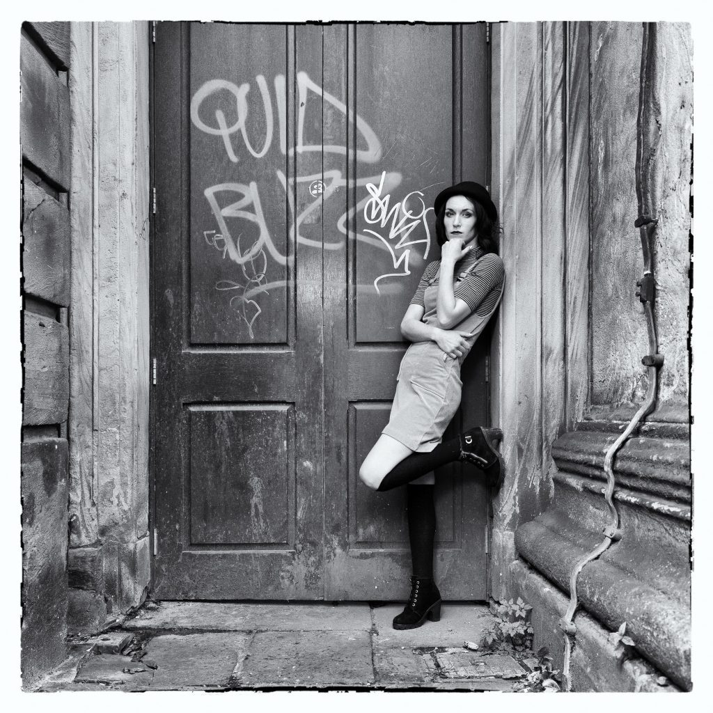 Black and White Photograph of Young Girl in a Doorway with Graffiti and taken at a Welshot Photographic Academy Workshop to Learn about Off Camera Flash for Beginners